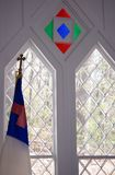 Window details in small church. The interior windows of a small church with clear and stained glass and a religious flag stock photo