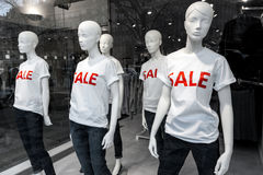Window display with mannequins and text Sale. Window display with five mannequins wearing t-shirts with text Sale Royalty Free Stock Photo