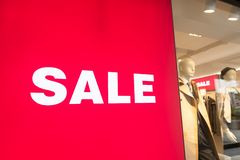 Window display with text SALE in a shop. Text Sale on red poster and Mannequins Standing In Store Window Display Of Women`s Casual Clothing Shop In Shopping Mall royalty free stock photography