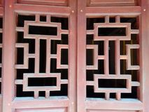 Window or door lattices, slightly open, wooden and red colored. Black doorway of ancient Vietnamese temple Royalty Free Stock Image