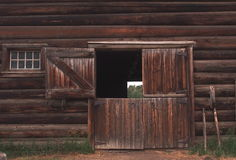 Window And Door In Wooden Barn. Multi-paned window and open door in wooden barn Royalty Free Stock Photography