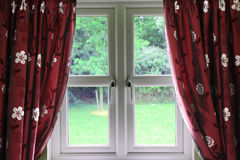 Window draped in curtains. Looking onto grass and trees Royalty Free Stock Photography
