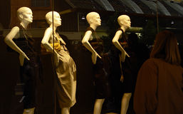 Window dressing. Mannequins displaying clothes at a store window royalty free stock photos