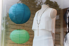 Window dressing. Headless mannequin in white dress behind glass Royalty Free Stock Images