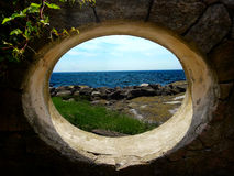 Window facing tidal pools and the ocean. The opening in a stone wall looks out over a tidal pool and the ocean Stock Photo