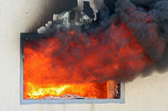 Window on Fire. Photo of huge flame distracting house on fire. Fire safety concept Stock Photo