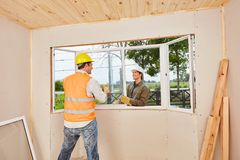 Window fitters installing new window. At construction site royalty free stock photos
