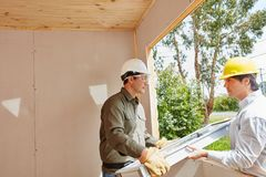 Window fitters mounting new window. In woodhouse stock photos