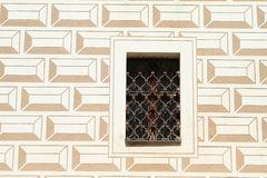Window with fittings on palace Breznice. Window with iron fittings on renaissance palace Breznice with renaissance envelopes on plaster in Czech Republic Stock Images