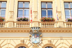 Window with flags and blazon. City blazon under window with flags and flowers on a house in town Prachatice (Czech Republic Royalty Free Stock Images
