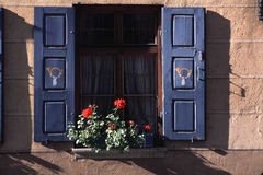 Window with floWer box in Germany. Typical window with shutters, a flower box and flowers in Germany.  Image was shot on Garmish PartenKirchen, Germany, Bavaria Stock Photography