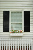 Window Flower Box. Pretty window flower box with black shutters and white picket fence royalty free stock photo