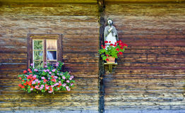 Window with flower decoration and figure of a saint Royalty Free Stock Photography