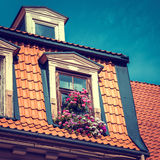 Window with flowerbox in old garret roof. Stock Photography