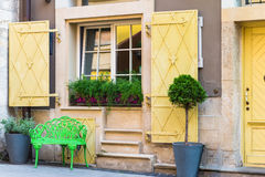 Window with flowerpots and paw. Window in old house decorated with flowerpots with green flowers and green paw Royalty Free Stock Photo