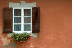 Window flowers. Window on red plaster building with flowers in window Royalty Free Stock Photos