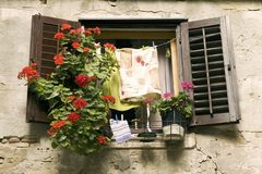 Window with flowers and laundry. A small window with red geranium flowers and drying laundry in Porec, Slovenia Stock Photo