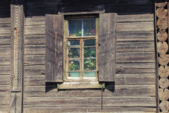 Window with flowers in wooden house , russian countryside Stock Photography