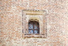 Window with forged bars in the historic tower built of red brick Royalty Free Stock Image