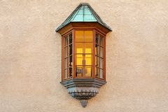 The window in the form of a bay window is located in the middle of the plastered wall of the building.  stock photo