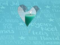 Window in the form of a heart with a turquoise candle and an international text christmas background. Turquoise window in the form of a heart with a emerald royalty free stock photos