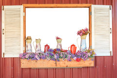 Window frame decorated by flowerpot hanging below and some flowers in vintage vase with white background inside. Window frame decorated by wooden flowerpot Royalty Free Stock Photo