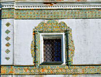 Window framed with colorful ancient mosaic tiles. Nicholas Vyazhischsky stauropegic monastery,Veliky Novgorod, Russia. Ornamental architecture, architecture Royalty Free Stock Images