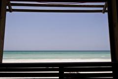 Window framed view. Open window overlooks ocean and horizon stock images