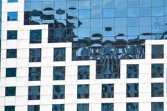 Window front of a modern building. The building`s fassade, with its knitted lines and rectangles, is intended to somewhat reduce the monotony of the glass Stock Photography