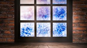 The window is frozen, frosty morning, snowflakes on the glass, an empty room with a window, an old brick wall and a wooden floor. Part of the background is a royalty free stock images