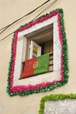 Window with garland and flag in Portugal. Stock Photo