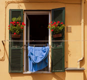 Window with geraniums and laundry Stock Images