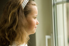 Window girl. A young girl looking through a window Stock Image