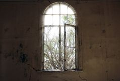 Window without glass and dirty walls in an abandoned house royalty free stock photo