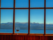 Window with glass of wine. Window overlooking the mountains with glass of wine - Bariloche - Argentina stock photo