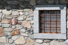 One stone window of a chalet with metal square grates royalty free stock image