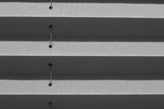 Window gray pleated blind close up with details. Window gray pleated blind close up with details in home interior. Structure and texture of fabric background Royalty Free Stock Images