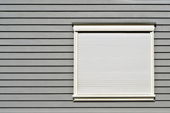 Window on Gray Wall. Abstract linear background from a modern building of a white window covered by blinds on a gray wooden wall stock image