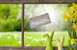 Window, Green Meadow, Auszeit Means Downtime. Sign With German Text Auszeit Means Downtime. Window Frame With View To Beautiful Sunny Green Meadow. Easter Bunny Royalty Free Stock Image