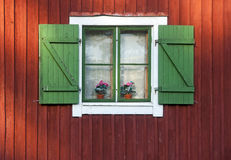 Window with green shutters. On red wooden wall Royalty Free Stock Photography