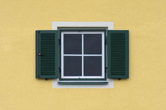 Window with green shutters. Yellow facade with window and green shutters Royalty Free Stock Image