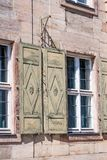 Window with green shutters in a facade of sandstone Royalty Free Stock Image