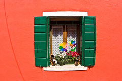 Window with green shutters on a red facade Stock Photography