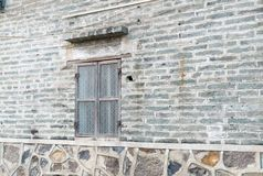 Window at grey brick and stone wall in perspective view Royalty Free Stock Images