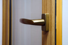 Window handle on fiberglass window. Gold color. Stock Photo