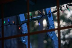 Window of home showing ladder and lights used for christmas decoration. Ladder leans up against home and window with christmas lights decoating the outdoors royalty free stock images