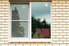 Window of the house. Window surrounded by brick wall with reflection Royalty Free Stock Images