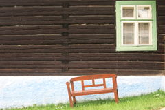 Window on the house and below the bench. Wooden window on the house and beneath crooked bench Royalty Free Stock Photos