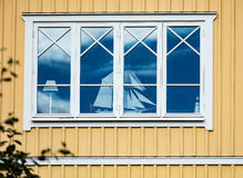 Window of a house with a model sailing boat. A reflection of blue sky Royalty Free Stock Photos