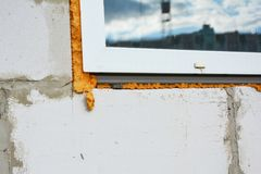 Window installation and insulation with spray foam insulation to avoid thermal bridge. Close up on Window installation and insulation with spray foam insulation royalty free stock photography